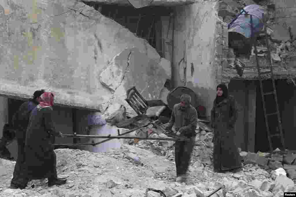 Civilians carry belongings from rubble after what activists said was shelling by forces loyal to Syrian President Bashar al-Assad, Jazmati, Aleppo, Jan. 23, 2014.