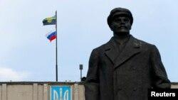 Sovet dövlətinin banisi Vladimir Leninin heykəlinin arxasındakı inzibati binada Donetsk separatçılarının və Rusiyanın bayraqları dalğalanır.