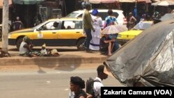 Un albinos mendie sur une avenue à Conakry, Guinée, 22 avril 2017. (VOA/Zakaria Camara)