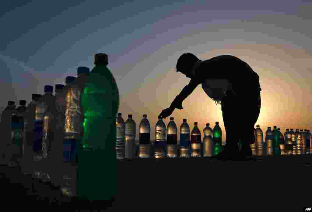 A boy arranging bottles of drinking water for sale at 10 PKR ($0.11) along Karachi's Clifton beach March 15, 2012. (Reuters)