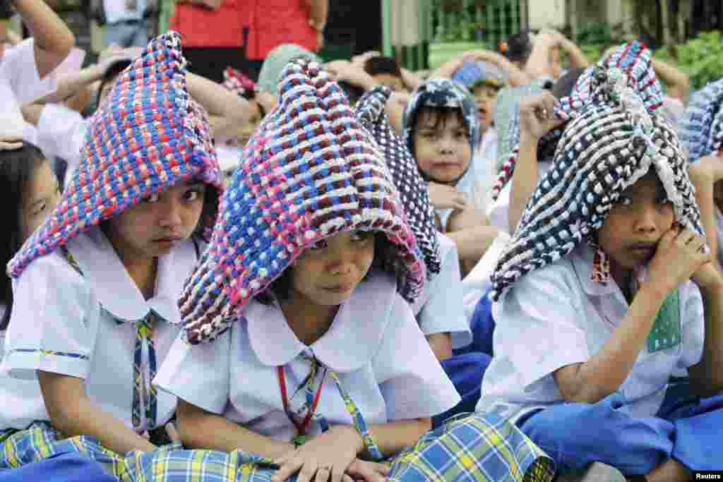Elementary school pupils use doormats as improvised protective headgear during an earthquake drill in Paranaque city, metro Manila. The drill aims to educate students and school staff on how to properly respond during high-intensity earthquakes.