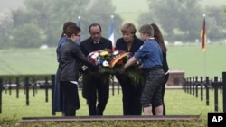 French President Francois Hollande, left, and German Chancellor Angela Merkel lay a wreath at a German cemetery in Consenvoye, northeastern France, May 29, 2016, during a remembrance ceremony to mark the centenary of the battle of Verdun.
