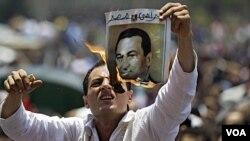 Seorang demonstran membakar poster mantan Presiden Hosni Mubarak di Lapangan Tahrir, Kairo (1 Juli 2011).
