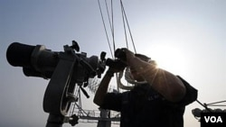 Seorang tentara meneropong dari atas kapal USS George Washington dalam latihan bersama Angkatan Laut AS-Korea Selatan di Laut Kuning.
