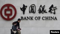 """Seorang pejalan kaki melewati kantor cabang """"Bank of China"""" di Beijing (Foto: dok). China diprediksi akan menjadi negara dengan ekonomi terkuat pada akhir 2014."""