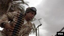 Seorang tentara Libya di kota Benghazi sedang mengisi amunisi senjatanya, Sabtu (26/2).