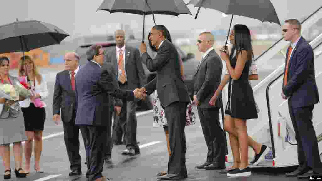 Le président américain, accompagné de sa femme Michelle et de leurs deux filles, Malia, 17 ans, et Sasha, 14 ans, sous une pluie battante, La Havane, 20 mars 2016