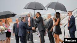 Presiden Obama (tengah) berjabat tangan dengan Menlu Kuba Bruno Rodriguez setibanya keluarga Presiden Amerika tiba di bandara Internasional di Havana, Kuba (20/3).