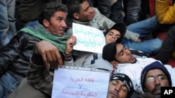 Tunisian protesters who walked from Sidi Bouzid, lay on the ground in front of the prime minister building in Tunis, 23 Jan 2011