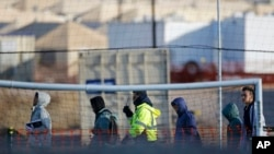 FILE - Teen migrants walk in line inside the Tornillo detention camp in Tornillo, Texas, Dec. 13, 2018. Thousands more migrant children may have been split from their families than the Trump administration previously reported.