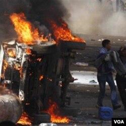Para demonstran membakar mobil dan gedung-gedung dalam protes di Kairo Jumat (28/1).