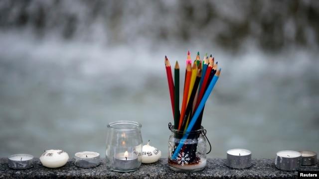 Những cây viết chì biểu trưng cho tự do bày tỏ ý kiến được đặt gần những cây nến trong khi dân chúng tụ họp để tưởng nhiệm các nạn nhân sau khi các tay súng tấn công tuần báo trào phúng Charlie Hebdo