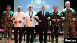 在马尼拉,美国和菲律宾官员在年度军演开幕式上手挽手(2016年4月4日)