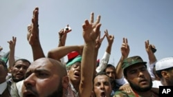 周五聚集在的黎波里烈士广场上的人们作出胜利的手势