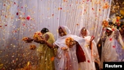Widows throw flowers into the air during a holi celebration at the Meera Sahavagini ashram in Vrindavan in the northern Indian state of Uttar Pradesh, Mar. 24, 2013.