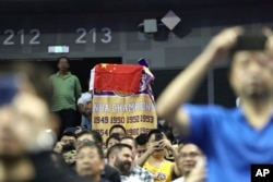 A fan drapes a Chinese national flag over an NBA banner during a preseason NBA basketball game between the Brooklyn Nets and Los Angeles Lakers at the Mercedes Benz Arena in Shanghai, China, Oct. 10, 2019.