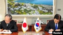 Južnokorejski ministar odbrane Han Min-ku i japanski ambasador u Južnoj Koreji Jasumasa Nagamine potpisuju sporazum u Selu, 23. novembar 2016.