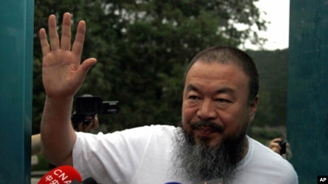 Dissident Chinese artist Ai Weiwei waves from the doorway of his studio after he was released on bail in Beijing, June 23, 2011. Ai was detained in April, igniting an international uproar.