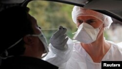 A medical worker administers a nasal swab to a patient at a drive-through testing site for coronavirus disease (COVID-19) near the hospital in Laval, France, July 15, 2020.
