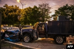 Bullet-ridden and crashed vehicles remain in a street of Culiacan, state of Sinaloa, Mexico, Oct. 17, 2019, after heavily armed gunmen in trucks fought an intense battle with Mexican security forces.