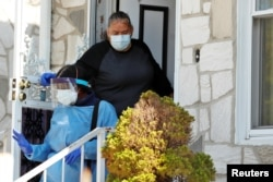 Home care nurse Flora Ajayi is thanked by a clients daughter as she departs from a home while wearing personal protective equipment (PPE) to protect herself and prevent cross-contamination while visiting a client, April 22, 2020.