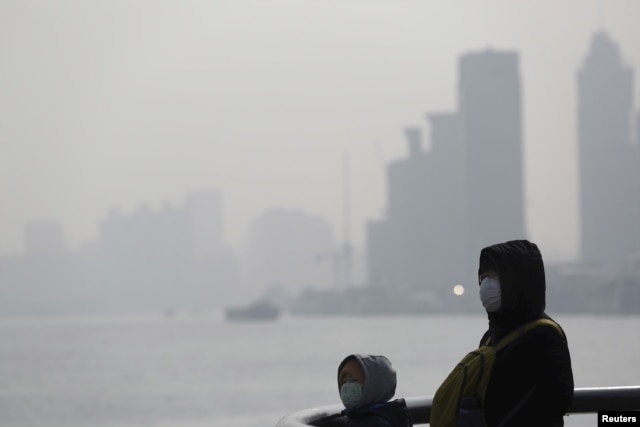 FILE - People wear protective masks near the Bund in Shanghai, China, Jan. 19, 2016. China's top court in January reaffirmed a record fine on six firms for discharging toxic waste acids into two rivers in Jiangsu province.