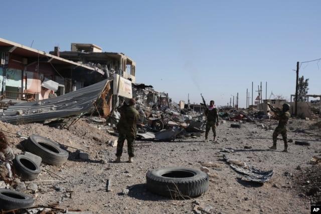 Kurdish peshmerga fighters fire into the the air while celebrating the retaking of of Sinjar, northern Iraq, Nov. 13, 2015.