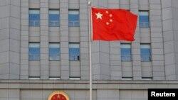 Bendera China berkibar di dekat lambang nasional China di Pengadilan Menengah Rakyat No. 2 Beijing, 11 September 2020. (Foto: Reuters)