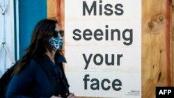 2020年4月1日新冠病毒爆发期间,一名戴着口罩的女士走过封闭的餐馆: 门上写着:想念你们。