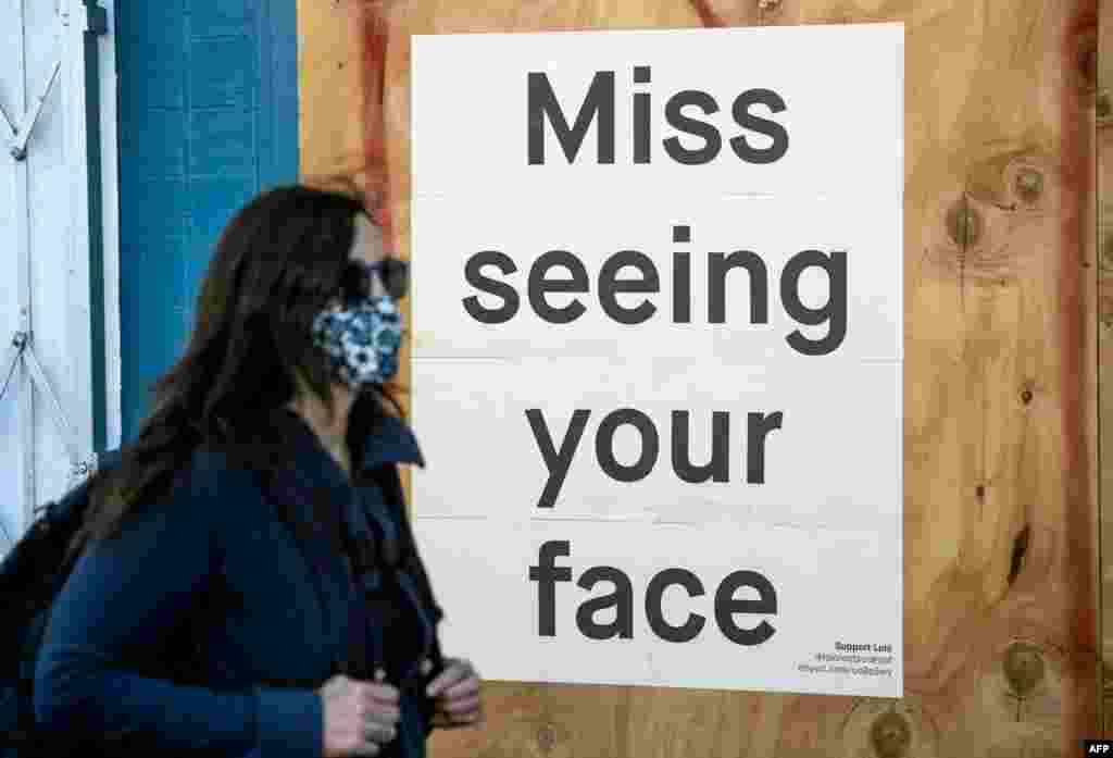 A woman in a face mask walks by a sign posted on a boarded up restaurant in San Francisco, California, April, 1, 2020, during the novel coronavirus outbreak.