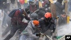 Manifestantes anti-governamentais protegem-se de um canhão d'água da polícia durante confrontos em Madrid, nos arredores de Bogotá, Colômbia, sexta-feira, 28 de Maio de 2021.