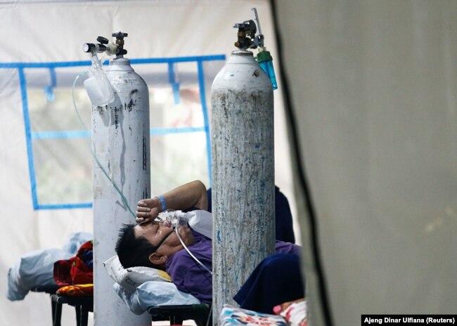 Seorang pasien COVID-19 bernapas dengan masker non-rebreather di tenda darurat sebuah rumah sakit di