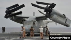 在美海军第三舰队主导的一次军演中,海军陆战队员检查一架降落在日本海上自卫队直升机驱逐舰的鱼鹰战机。