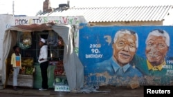 FILE - Youths stand outside a makeshift shop near murals of former South African president and anti-apartheid hero Nelson Mandela in Soweto, Johannesburg, South Africa.