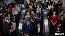 Orang-orang memasuki stasiun subway di People's Square, Shanghai (foto: REUTERS/Carlos Barria)