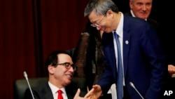 美財政部長努欽6月8日在日本20國集團財長會議上與中國央行行長易綱握手。