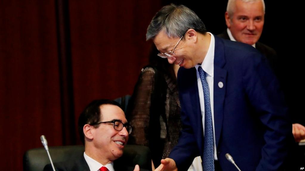 美国财政部长姆努钦与中国银行行长易纲星期六(2019年6月8日)在日本20国财长与央行行长会议期间握手。
