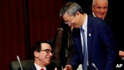 美國財政部長姆努欽與中國銀行行長易綱星期六(2019年6月8日)在日本20國財長與央行行長會議期間握手。