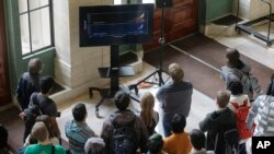 Massachusetts Institute of Technology students gather around a monitor in an overflow area on the MIT campus to watch an update by scientists on the discovery of gravitational waves, Thursday, Feb. 11, 2016,