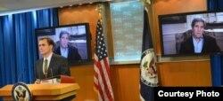 克里国务卿通过视讯从波士顿欢迎正式在简报室登场的新任发言人柯比(照片:美国国务院)