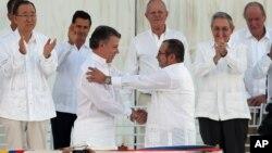 Presiden Kolombia Juan Manuel Santos (depan kiri) berjabat tangan dengan Komandan tertinggi FARC, Rodrigo Londono, setelah penandatangan kesepakatan perdamaian di Havana, Kuba, 26 September lalu. Pemilih Kolombia hari Minggu (2/10) menolak kesepakatan damai ini.