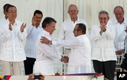 Colombia's President Juan Manuel Santos, front left, and the top commander of the Revolutionary Armed Forces of Colombia (FARC) Rodrigo Londono, known by the alias Timochenko, shake hands after signing the peace agreement between Colombia's government and the FARC to end over 50 years of conflict in Cartagena, Colombia, Sept. 26, 2016.