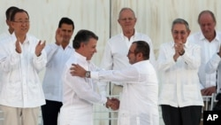 후안 마누엘 산토스(가운데 왼쪽) 콜롬비아 대통령이 지난달 26일 카리브 해안도시 카르타헤나에서 반기문(왼쪽) 유엔사무총장 등 국제사회 지도자들이 지켜보는 가운데 로드리고 론도뇨(가운데 오른쪽) 콜롬비아 무장혁명군(FARC) 최고사령관과 함께 평화협정에 서명한 뒤 악수하고 있다.