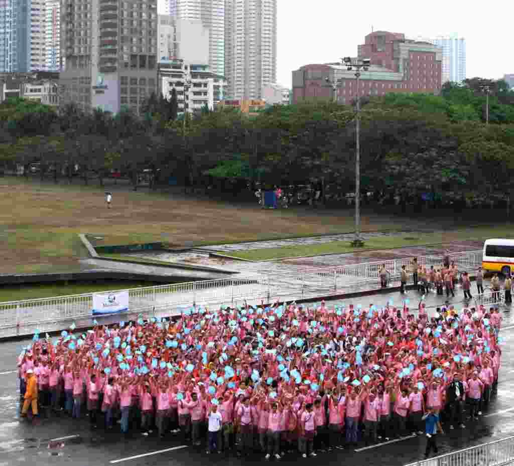 Cientos de personas intentan formar una gota de agua al frente de la Tribuna de Quirino en Manila, Filipinas, como parte de la celebración del Día Mundial del Agua.
