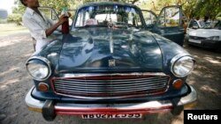 A driver stands next to his parked Ambassador car, manufactured by Hindustan Motors,