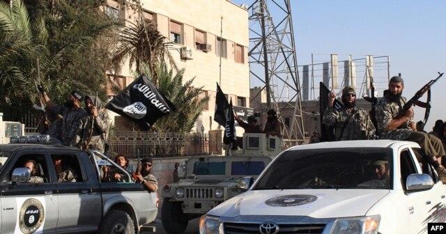 Chiến binh Nhà nước Hồi giáo diễu hành trên đường phố ở Raqqa, Syria.