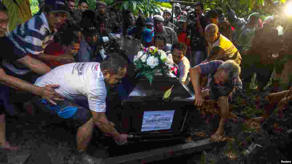 Relatives lower the coffin containing the body of Hayati Lutfiah, a passenger of AirAsia Flight 8501, during her burial at a cemetery in Surabaya, Jan. 1, 2015.