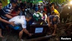 Thân nhân hạ huyệt quan tài của bà Hayati Lutfiah, một hành khách trên chuyến bay AirAsia 8501, tại một nghĩa trang ở Surabaya, ngày 1/1/2015.