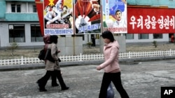 """North Koreans walk past posters reading """"Forward to the ultimate victory under the leadership of the great party!"""" on March 19, 2013 on a street in Phyongchon District in Pyongyang."""