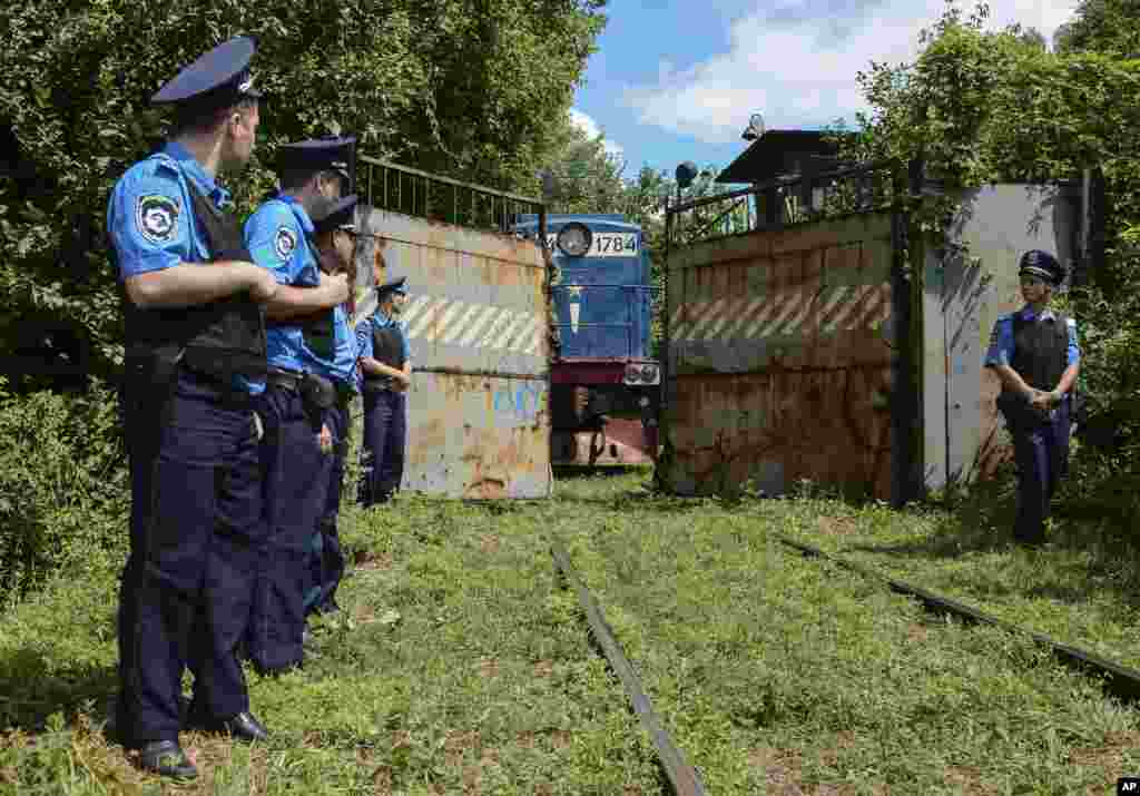 Police officers secure a refrigerated train loaded with bodies of the passengers of Malaysian Airlines flight MH17 as it arrives at a Kharkiv factory for a stop, July 22, 2014.